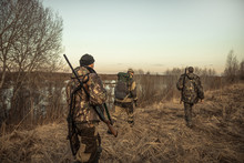 Hunting Scene With Group Of Hunters With Hunting Ammunition Going Through Rural Field During Hunting Season At Sunset