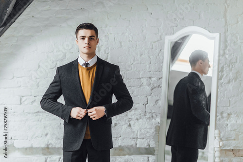 Photo Serious businessman in yellow sweater  and black blazer standing at modern home and looking to the  camera