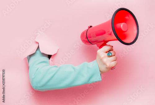 Ręka w klasycznej niebieskiej kurtce z megafonem