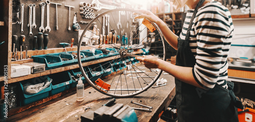 Fotografía  Cute Caucasian female worker holding and repairing bicycle wheel while standing in bicycle workshop