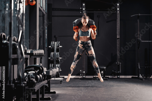 Fototapeta premium Full length of Caucasian female bodybuilder jumping with bulgarian sack on shoulders. Night workout in gym concept.