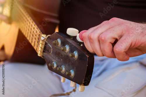 Fotografiet  Close up of a male person tuning his acoustic guitar.