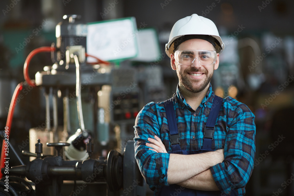 Fototapeta Waist up portrait of bearded factory worker wearing hardhat looking at camera while standing in workshop, copy space