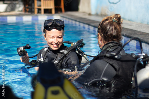 Fototapeta Female diving instructor teaches student to scuba dive in swimming pool. Lady getting first experience with scuba diving under the guidance of experienced recreational diving instructor on vacation. obraz