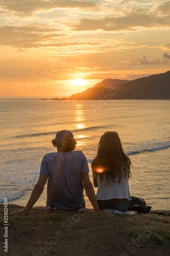 In de dag Kamperen Young romantic couple on vacation sitting and watching colorful sunset over the sea coast.