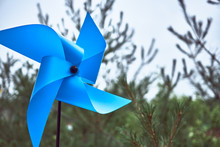 A Blue Pinwheel In Front Of A Field Of Pinetree At An Elementary School In South Korea.