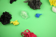 canvas print picture - lot of crumpled used colored plastic bags on green background, big ecological problem