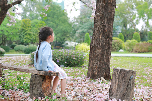 Fotografía  Peaceful little girl sitting on wood log in the summer garden with looking out