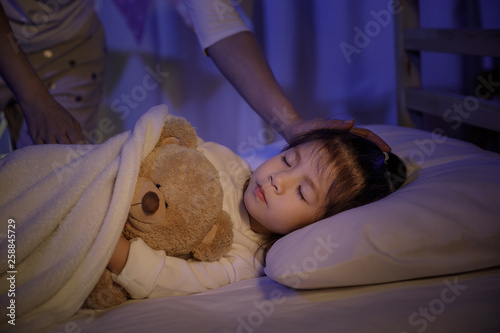 Fotografia  Mother putting blanket on and stroking head for her little girl daughter on bed