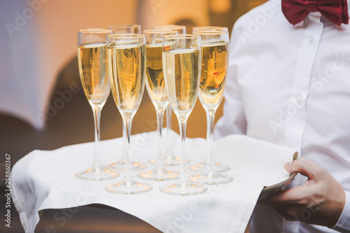 Waiter serving champagne glasses on a tray in a restaurant. Anniversary celebration concept.