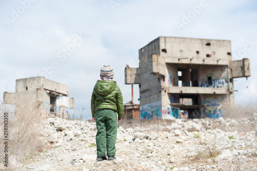 Fototapeta one little lonely child in green jacket standing on ruins of destroyed buildings