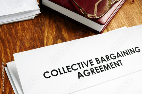 Photo Collective bargaining agreement and note pad with glasses.