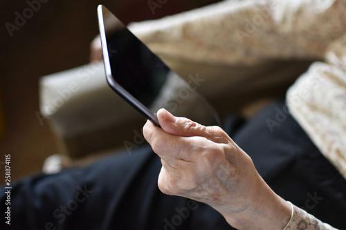 Fotografia, Obraz  Old wrinkled hand holding tablet