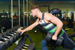 muscular man training in the gym. young guy picks up a dumbbell near the mirror.