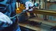 Mechanic is working with metal in a workshop, making measurements of metal parts. Worker holds a caliper in his hand, in a special suit on factory background.