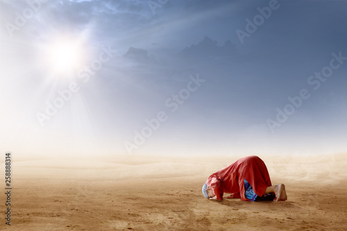 Photo  Rear view of asian muslim man praying in prostration position on desert
