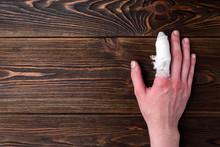 Injured Painful Finger With White Gauze Bandage On Dark Wooden Background.