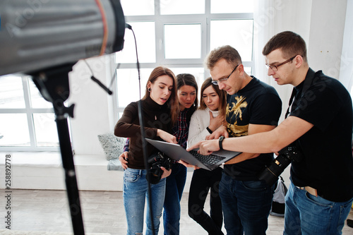 Fotografía  Photographer explaining about the shot to his team in the studio and looking on laptop