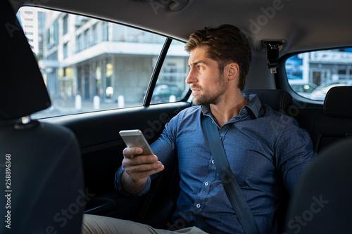 Fototapeta Man sitting in car using smart phone obraz