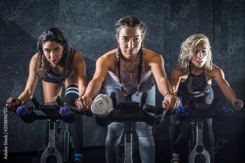 Group of young sporty women riding cycling bikes during spinning class indoors