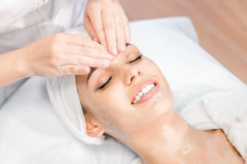 Fototapeta na wymiar Cosmetology. The hands of a cosmetologist do a facial massage with a mask. Smiling girl on spa procedure. Facial treatment.