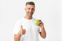 Portrait Of Healthy Man 30s Having Bristle In Casual T-shirt Posing On Camera And Holding Green Apple In Hand