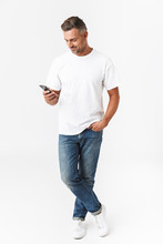 Full Length Image Of Brunette Man 30s Wearing Casual T-shirt And Jeans Using Mobile Phone While Holding In Hand