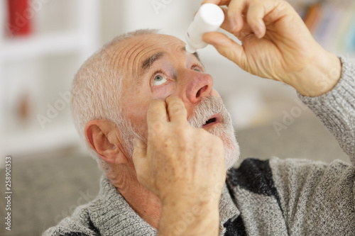 Fotomural senior man dripping a red eye with eye drops