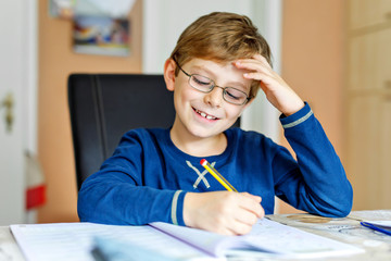 Naklejka na ściany i meble Portrait of cute school kid boy wearing glasses at home making homework. Little concentrated child writing with colorful pencils, indoors. Elementary school and education