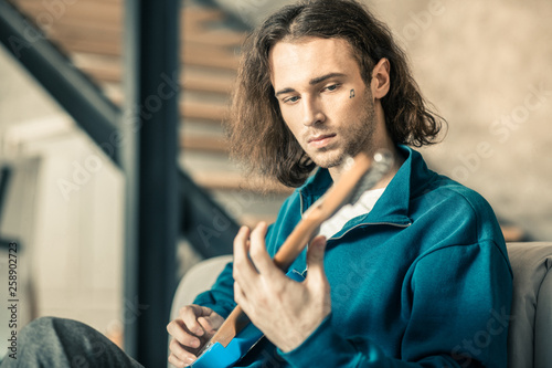 Vászonkép Emotionless long-haired unusual guy starting his musical repetition