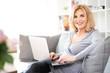 canvas print picture - Lächelnde ältere Frau auf der Couch am Laptop schaut in die Kamera