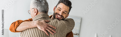 Fotografiet panoramic shot of happy bearded man smiling while hugging elder father at home