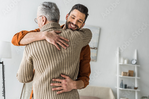 Photo  happy bearded man smiling while hugging elder father at home