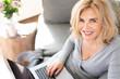 canvas print picture - Lächelnde ältere Frau arbeitet Zuhause auf der Couch am Laptop
