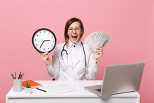 Female Doctor Sit At Desk Work On Computer With Medical Document Hold Money In Hospital Isolated On Pastel Pink Wall Background. Woman In Medical Gown Glasses Stethoscope. Healthcare Medicine Concept.