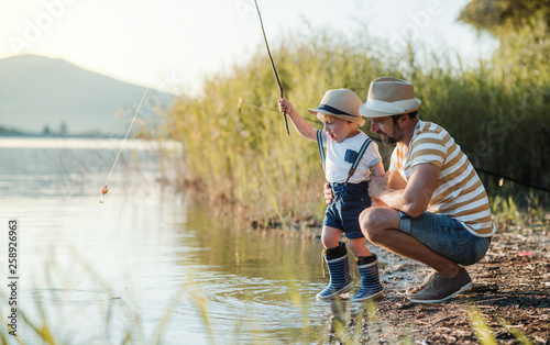 Foto auf AluDibond Fischerei A mature father with a small toddler son outdoors fishing by a lake.
