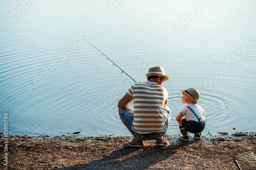 Leinwand Poster A rear view of mature father with a small toddler son outdoors fishing by a lake