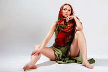 Stylish Photo Of Fashion Folk Woman In Colorful Dress And Red Scarf Warp On Head, Sitting On The Floor, Posing On Gray Backgroun