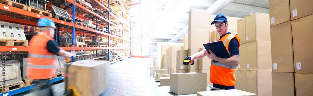 Fototapeta Lagerung und Logistik im Handel - Arbeiter in einer Logistikhalle