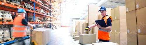 Slika na platnu Lagerung und Logistik im Handel - Arbeiter in einer Logistikhalle