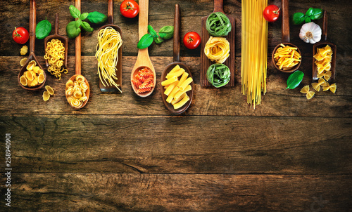Foto  Various pasta on wooden spoons on wooden background
