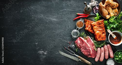 Fototapeta Various kinds of grill and bbq meats with vintage kitchen and butcher utensils obraz