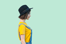 Profile Side View Portrait Of Pretty Young Hipster Girl In Blue Denim Overalls, Yellow Shirt And Black Hat Standing, Smiling And Looking Straight. Indoor Studio Shot Isolated On Light Green Background