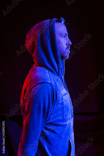 Fotografía A male model with stubble wearing a hood up in a dark atmospheric future colour setting