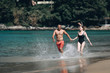 Couple Running Through Waves On Beach Holiday. Phuket. Thailand