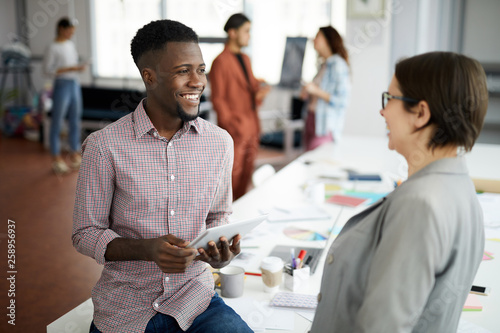 Portrait of handsome African-American man talking to colleague and smiling  whil Canvas Print