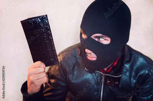 Fotomural Young ill-intended man wearing black mask holds the black leather women purse and looks to his loot