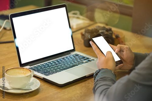 Photo  Close up hand of asian young freelance using laptop and smartphone for working with his job in coffee shop at the night