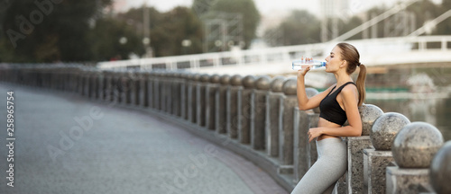 фотографія  Sporty millennial woman drinking water after run practice on bridge