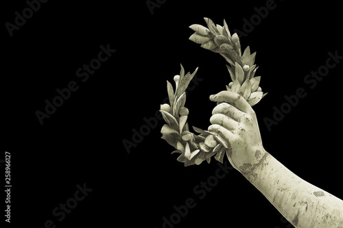Fotografie, Obraz  Hand holds a laurel wreath - bronze statue on black background - Success and fam